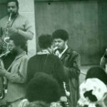 Rahsaan Roland Kirk performing in Horace Tapscott class at Riverside Community College, May 1971. L to R: Larry Northington, alto sax; Arthur Blythe, alto sax; Will Connell, alto sax; Kirk (back to camera); Azar Lawrence, sax; Butch Morris, cornet. (© Michael Dett Wilcots)