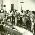 The Arkestra in performance at the IUCC, 1979/1980. L to R: Horace, piano/conductor; David Bryant, bass; Adele Sebastian, flute; Louis Spears, cello; Fritz Wise, drums; Michael Session, soprano sax; Aubrey Hart, alto sax; Sabir Mateen, tenor sax; Lester Robertson, trombone; Dadisi Komolafe, tenor sax; Herbert Callies, alto clarinet; Fundi Legohn, French horn (© Mark Weber)