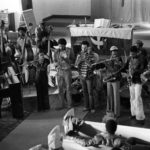 The Arkestra in performance at the IUCC, 1979/1980. L to R: Horace, piano/conductor; David Bryant, bass; Eugene Ruffin, bass; Adele Sebastian, flute; Kamonte Polk, bass; Ali Jihad, archivist/recorder; Jesse Sharps, soprano sax; Steve Smith, trumpet; Ishmael Balaka, drums; Dadisi Komolafe, flute; Michael Session, alto saxophone; Bill Madison, drums; Wendell Williams, french horn; James Andrews, tenor sax; Herbert Callies, alto clarinet (©. Mark Weber)