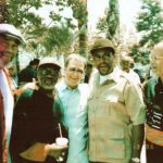 A gathering in Leimert Park, 2006, l to r – poet Kamau Daáood, artist John Outterbridge, writer Steven Isoardi, dj & producer Aman Kufahamu, artist Dale Davis, saxophonist and Arkestra leader Michael Session in back (© Clint Rosemond)